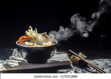 Noodles with steam and smoke in bowl on dark background, selective focus. Asian meal on a table, junk food concept