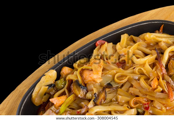 Noodles (udon) with Seadood over black background