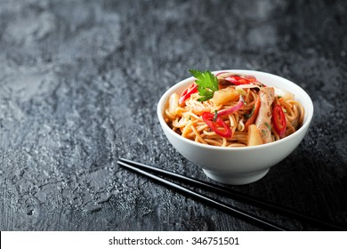 Noodles with vegetables, chicken and pineapple in sweet and sour sauce, selective focus
