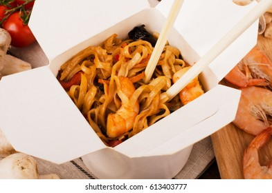 Noodles with vegetables, shrimp with chopsticks on a dark wooden background in a white box