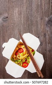 Noodles with vegetables, shrimp, green onions in sweet and sour Sauce with chopstikks on a dark wooden background in a white box. Selective focus.
