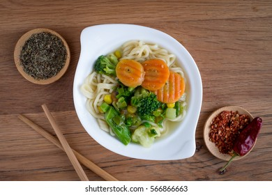 Noodles with vegetables and spices on a wooden background