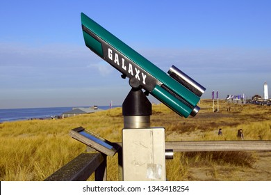 Noordwijk, the Netherlands - Januari 20, 2019: Green Galaxy tourist binoculars against a blue partly clouded sky.