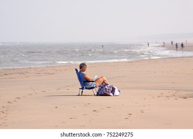 Noordwijk, the Netherlands, June 22, 2017: A woman sits all alone in a chair at the beach of Noordwijk, reading a book. In the background some more people strolling along the surf