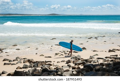 NOOSA, AUSTRALIA - MARCH 11; Surfer carrying a blue long-board heads to the water to complete in the Noosa Festival of Surf on March 11, 2014 at Noosa, Australia.