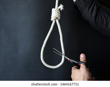 Noose on the neck. Man holding scissors in hands. Suicide concept. Hanging because of work stress. Depression or burnout. Terrible life situation. Life choice.