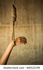 Noose in prison and wall grunge grain texture,Loop of old rope on wall background, Suicide Concept Image in Studio with Vignette Lighting and Copy Space.