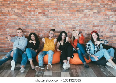 Nope. Group of close friends colleagues sitting on bean bags thumbs down. Denial and refusal. Disapproval and rejection.