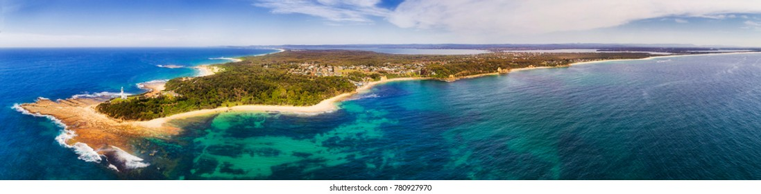 Norah head lighthouse and nature reserve on Central coast of NSW in wide aerial panorama. Clear pacific ocean water breaks at sandy beaches and seafloor of continent shore.