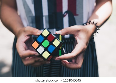 Norala, PH – October 31, 2017: Rubik's Cube was invented in 1974 by Hungarian sculptor and professor of architecture Erno Rubik. Young lady's hands playing a colorful rubik cube. Closeup.