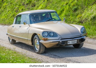 nord of MANZANO, ITALY - march, 2018: family walking in countryside on beige vintage car