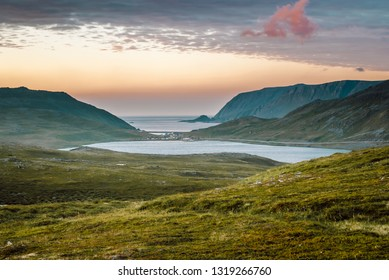 Nord summer Norwegian landscape behind the polar circle with green hills, sea bay, lake and camp village near North Cape (Nordkapp), Finnmark, Norway.