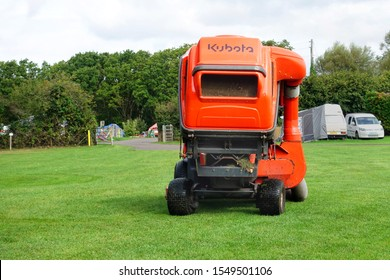 Norden, England - Aug 29 2018: Large orange Kubota Turbo lawnmower being driven around an English campsite to keep the grass tidy and in good condition