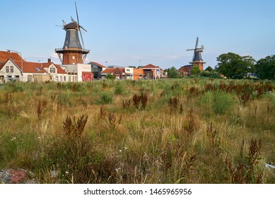 Norden, Germany - July 28, 2019: two historic wind mills behind a brownfield area in front of blue sky