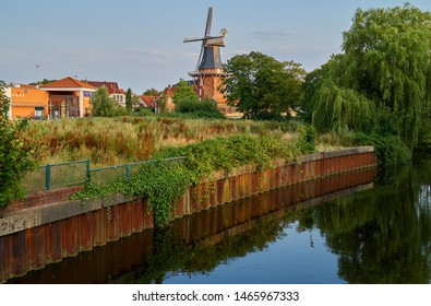 Norden, Germany - July 28, 2019: historic wind mill called dike mill behind a brownfield area and the water of the Norder Tief