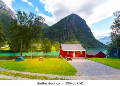Nordfjord in Norway. Norwegian red colorful wooden house and landscape with turquoise fjord water, mountains