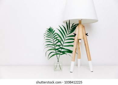 Nordic living room. Scandinavian lamp and tropical leaves. Eclectic Minimal home decor