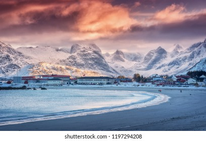 Nordic sandy beach with blue sea in winter at sunset in Lofoten islands, Norway. Landscape with snowy mountains, dramatic sky with orange clouds, water, village with buildings, walking people. Nature