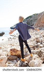 Nordic tourist young man on coastal beach destination, contemplative stretching arms on sunny sky summer holiday, nature outdoors. Healthy wellness living, leisure recreation lifestyle, exterior.