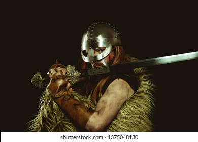 Nordic, Viking warrior with metallic helmet and animal skins. leather gauntlets, red wooden shield with gold decorations and steel sword
