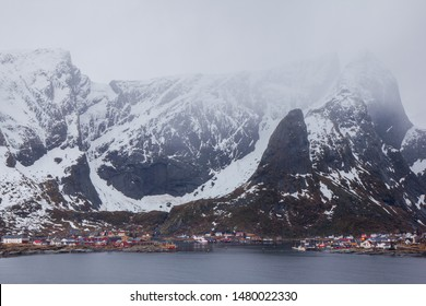 Nordic village under huge mountain range, partly covered in snow. Moody view of very well-known location and popular for many hikers and adventurers.