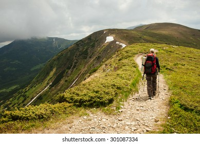 Nordic walk on the mountain road. Woman with trekking sticks under the clouds