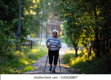 Nordic walking. Elderly woman with ski poles is on the road. (90 years old)