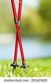 Nordic walking equipment. Closeup of red sticks on the green grass in the park. Active and healthy lifestyle.