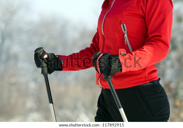 Nordic walking exercising. Woman power walking with hiking stick in winter nature outdoors. Focus and closeup on hands.