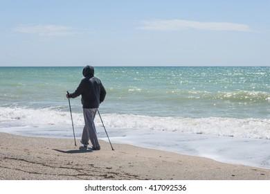 Nordic walking. Man hiking on the beach in Yevpatoriya (Evpatoria), Crimea. Active and healthy lifestyle.