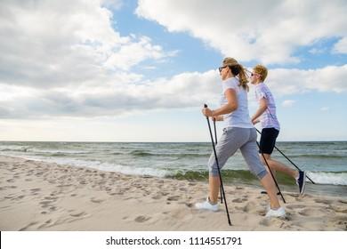 Nordic walking - man and woman training on beach