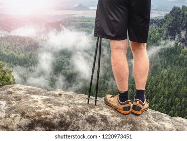 Nordic walking sticks and naked legs in sport shorts. Body  of a mountain hiker with hiking boots on a rock.