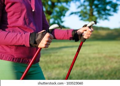 Nordic walking in summer. Closeup of woman's hand holding nordic walking poles