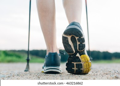 Nordic walking in summer. Closeup of woman's legs with nordic walking poles