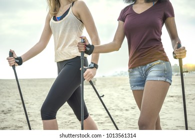 nordic walking, two girls walking on beach with sticks. concept of diversity and fitness