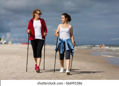 Nordic walking - two women  training on beach