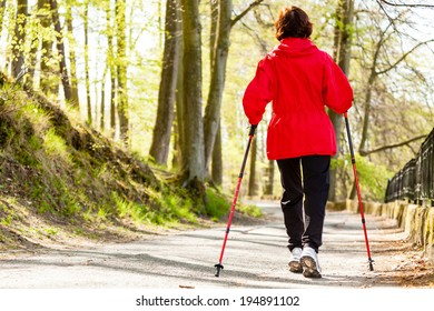 Nordic walking. Woman hiking in the forest or park. Active and healthy lifestyle.