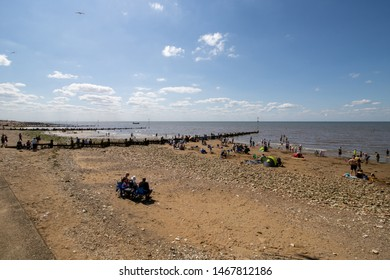 Norfolk Hunstanton, 1st August 2019: The beautiful beach front of the British seaside town of Hunstanton in Norfolk showing people and families having sun on the sandy beach on a bright sunny day.