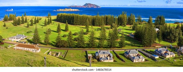 Norfolk Island, South Pacific, Australia.  Norfolk Island golf course lined with norfolk island pines. In the foreground are buildimgs from the convict period of the 1820's.