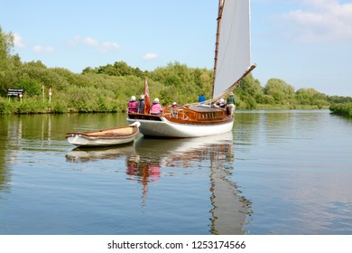 NORFOLK, UK - SEPTEMBER 6,2018: Vintage style sail boat towing a small rowing boat on the Norfolk Broads, Norfolk Broads, Norfolk, UK
