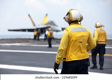 NORFOLK, VA - JUNE 27: Flight deck crew known as Yellow Shirts watch as an F18 is positioned on the deck of the USS Harry S. Truman on June 27, 2014. The aircraft carrier is stationed in Norfolk, VA.
