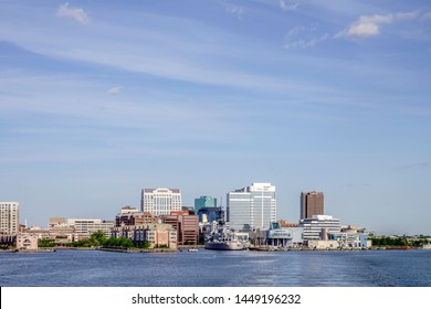 NORFOLK, VA/USA - MAY 15, 2019: Elizabeth River view of downtown waterfront, including USS Wisconsin battleship (now a museum); Nauticus, a maritime science center; and various commercial skyscrapers.