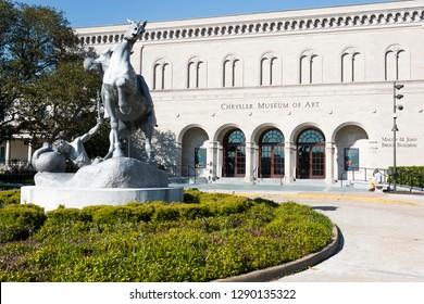 """NORFOLK, VIRGINIA - MAY 2, 2015:  The Chrysler Museum of Art, originally founded in 1933, with the sculpture """"The Torchbearers"""" by Anna Hyatt Huntington."""