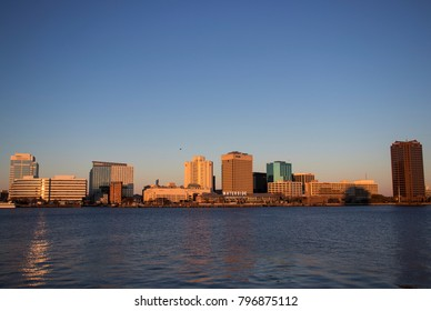 NORFOLK, VIRGINIA, USA - JANUARY 18, 2018: - The skyline of downtown Norfolk at sunset, viewed from Portsmouth.
