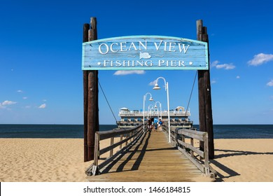 NORFOLK, VIRGINIA/USA - JULY 22, 2019:  Entrance sign for the Ocean View fishing pier, with the restaurant and bait shop in the background. The pier stretches out 1690 feet over the Chesapeake Bay.
