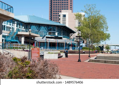 NORFOLK, VIRGINIA/USA - MAY 2, 2015:  A couple embraces in the rear of the Waterside attraction, an entertainment and dining venue built on the Elizabeth River.