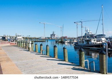 NORFOLK, VIRGINIA/USA - MAY 2, 2015:  People stand on a dock waiting to board a vessel at the Waterside Marina, with views of nearby Navy vessels on the Elizabeth River.