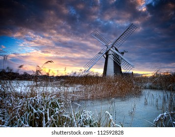 Norfolk windmill in reed bed and fenlands covered in snow with heavy skies