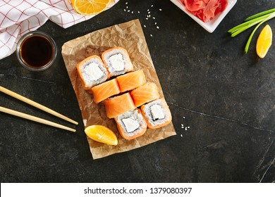 Nori Maki Philadelphia Sushi Rolls Set with Raw Salmon and Cream Cheese on Black Stone Table Background with Place for Text. Uramaki or Futomaki Sushi with Red Fish, Soy Sauce and Lemon Top View