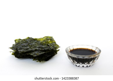 Nori sheets and  bowl with soy sauce   on white background.Crispy Dried seaweed.Asian cuisine. Food background with copy space.